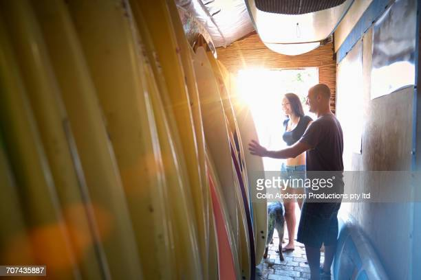 Man and woman examining surfboards in shop