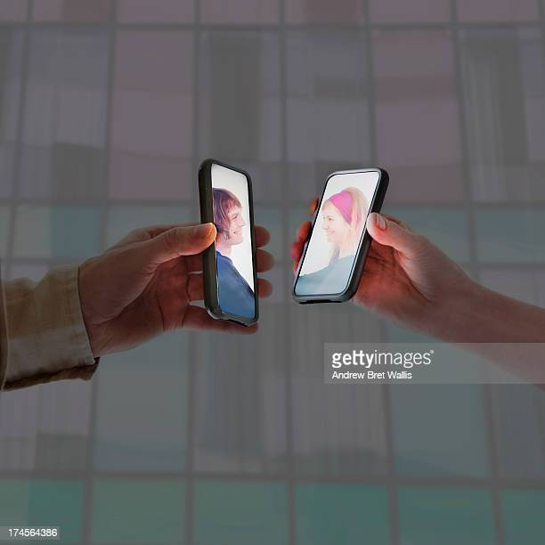 Man and woman face to face on mobiles