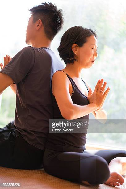Man and woman facing back while practicing yoga