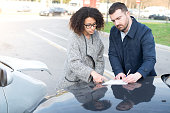 Man and woman filling an insurance car form after bad car crash
