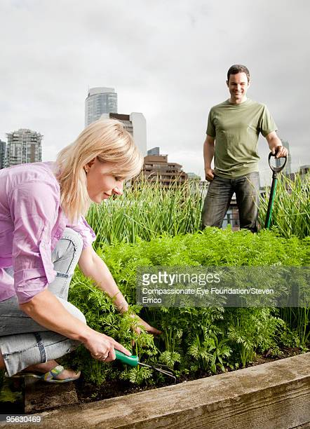 man and woman gardening in city