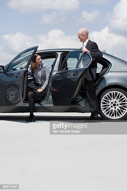 man and woman getting out of car
