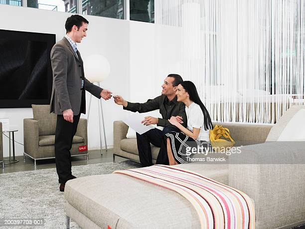 Man and woman giving credit card to salesclerk in furniture store