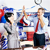 Man and woman giving each other high-five in campaign office, smiling