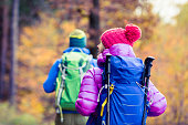 Man and woman couple hikers trekking in yellow autumn woods and mountains. Young people walking on trek trail with backpacks, healthy lifestyle adventure, camping on hiking trip, Poland.