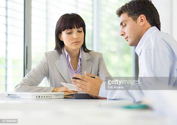 Man and woman having discussion in office