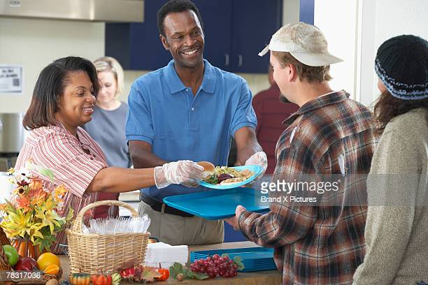 Man and woman helping in soup kitchen