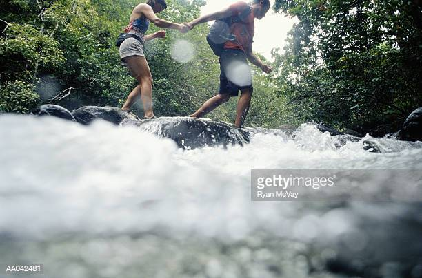 Man and woman hiking across river, low angle view