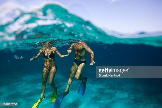 A man and woman hold hands in clear, blue water