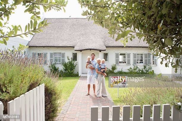 Man and woman holding babies in front of house with sold sign and white fence