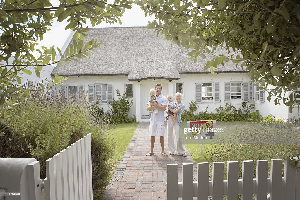 Man and woman holding babies in front of house with sold sign and white fence : Stock Photo