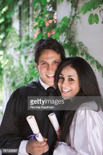 Man and woman holding college diplomas : Stock Photo