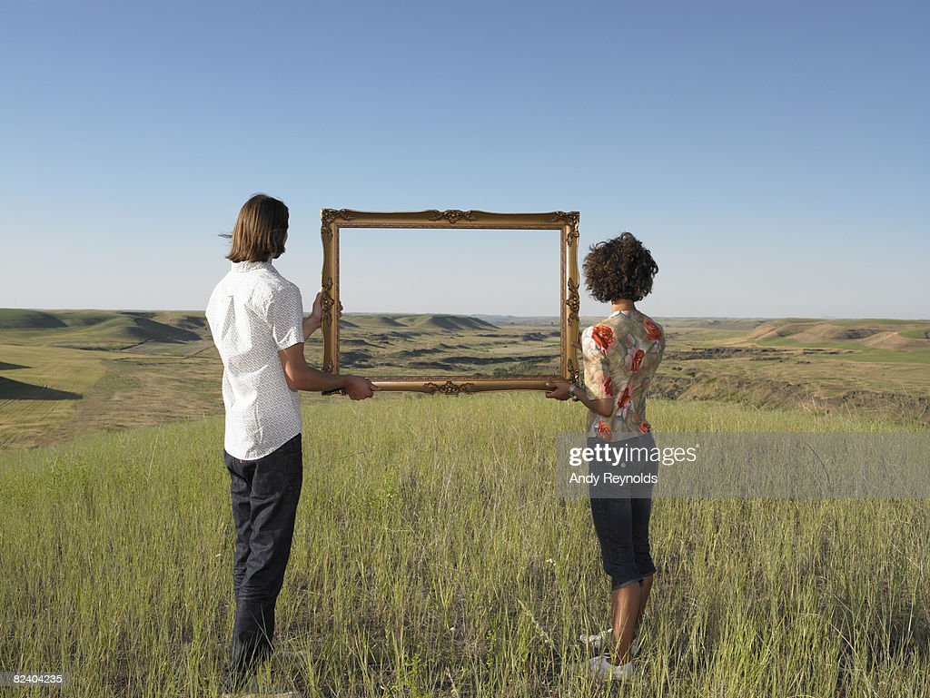 man and woman holding frame in open land