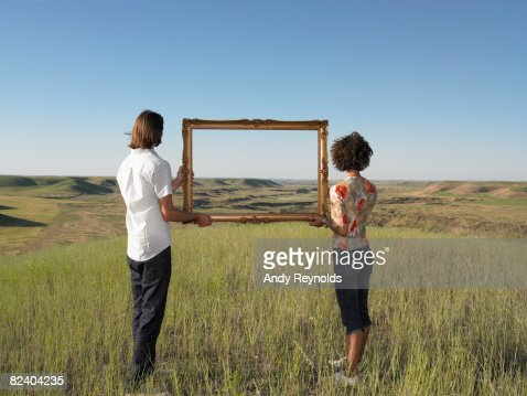 man and woman holding frame in open land : Stock Photo