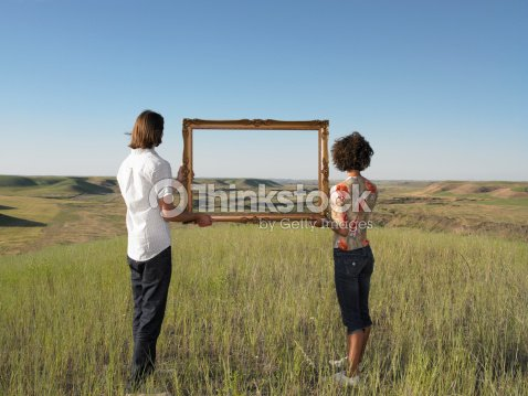 Man And Woman Holding Frame In Open Land Stock Photo | Thinkstock
