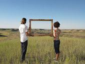 Hombre y mujer sosteniendo en tierra de bastidor abierto