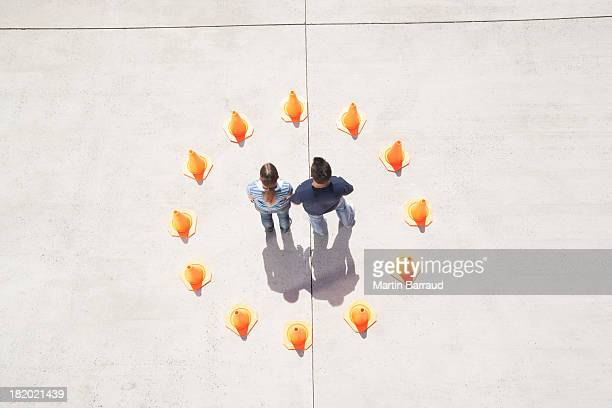Man and woman holding hands in circle of traffic cones