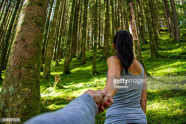 Man and woman holding hands in forest