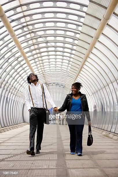 Homme et Femme tenant mains dans tunnel de lumière