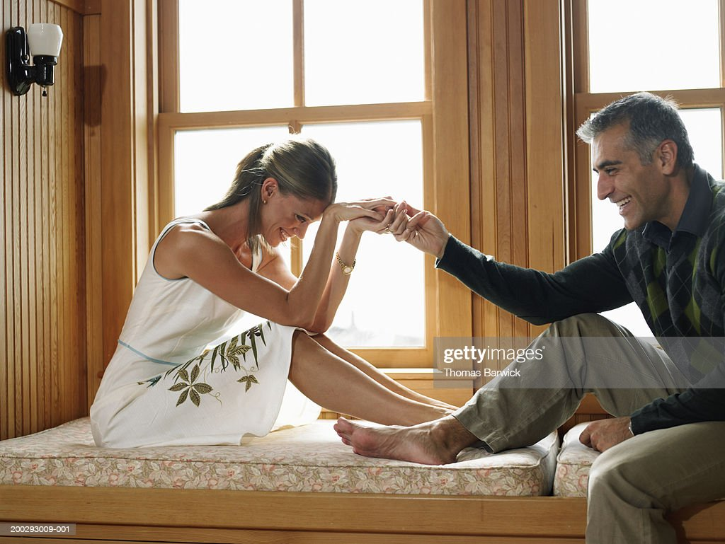 Man and woman holding hands on window seat, laughing, side view