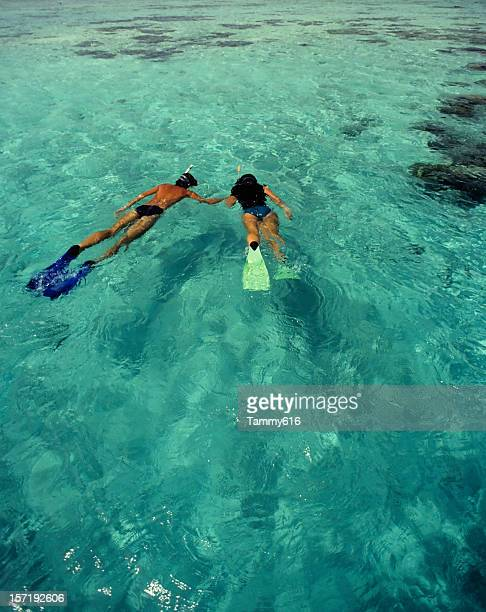 Man and woman holding hands snorkeling in the sea