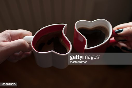 Man and woman holding heart shaped cups with coffee : Stock Photo