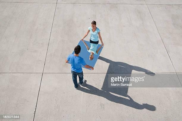 Homme et Femme tenant un miroir et réflexion
