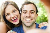 man and woman holding mobile to take selfie