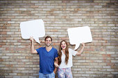 man and woman holding speech bubbles