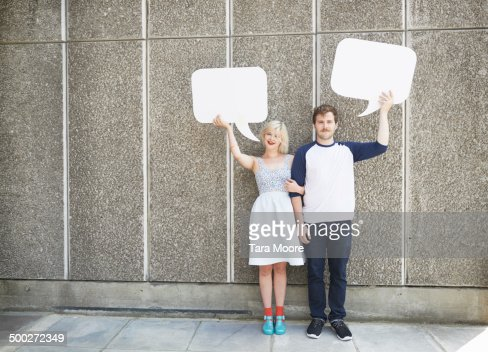 man and woman holding up speech bubbles