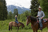 Man and woman horseback riding, mountain in background