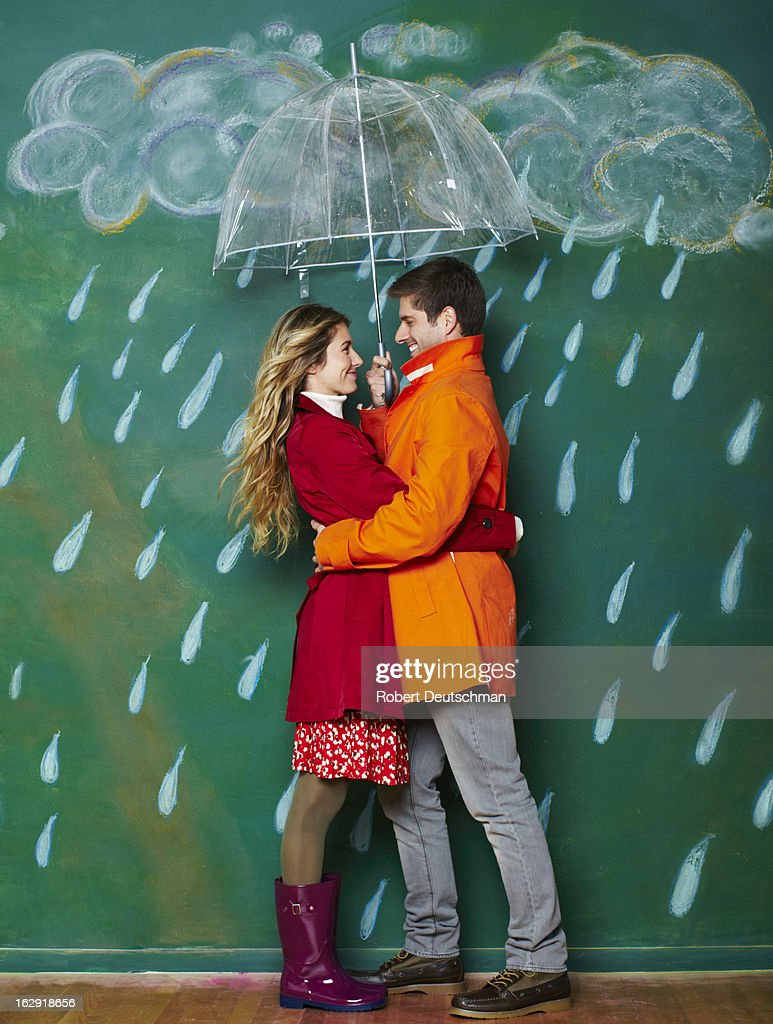 A man and woman hugging in the rain.