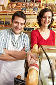 Man and woman in bakery, woman holding baguette, smiling, portrait