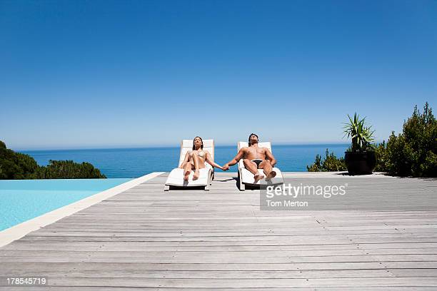 Man and woman in deck chairs sunbathing, holding hands