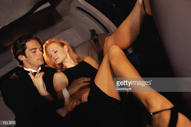 Man and woman in evening wear sitting in limousine