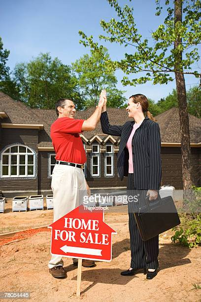 Man and woman in front of house with for sale sign