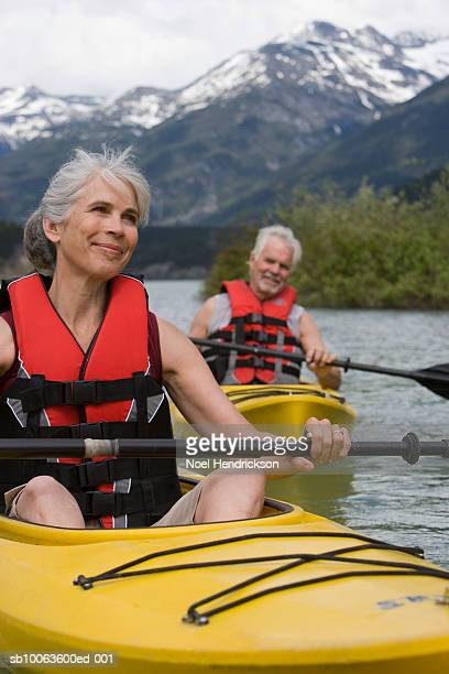 Man and woman in kayaks, wearing life jackets, mountain range in background