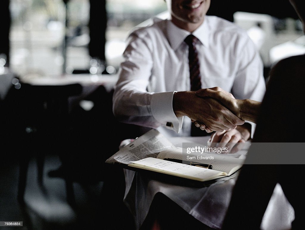 Man and woman in restaurant shaking hands : Stock Photo