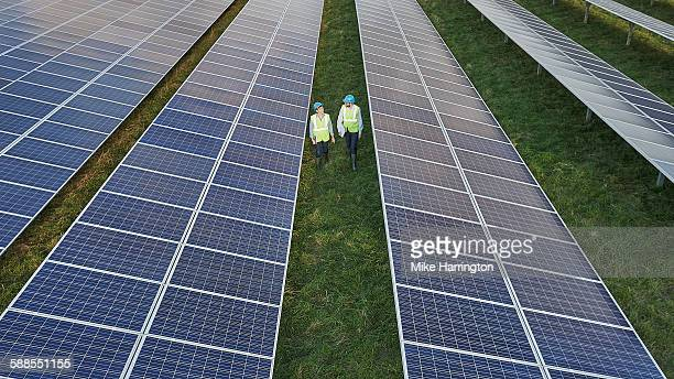 Man and woman in solar field wearing safety gear