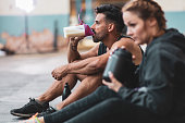 A man and a woman in sports clothing making and drinking protein drinks while sitting on the concrete floor.