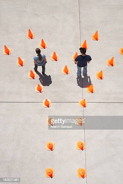 Man and woman in traffic cones moving apart