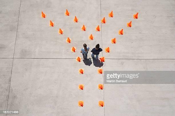 Homem e mulher em cones de trânsito de ir além