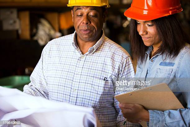 Man and woman in warehouse with blueprint and clipboard
