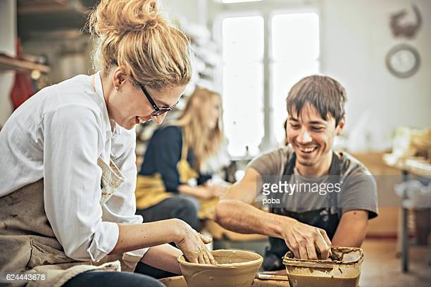 Man and woman in workshop working on pottery wheel