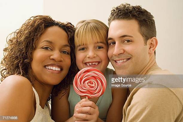 Man and woman indoors with girl holding lollipop
