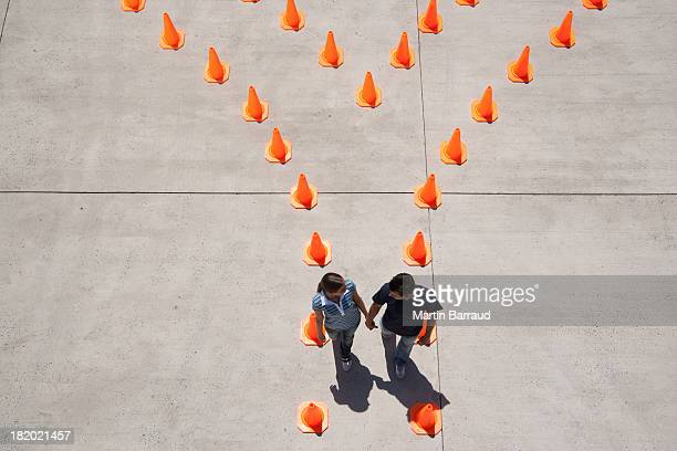 Man and woman inside traffic cones holding hands