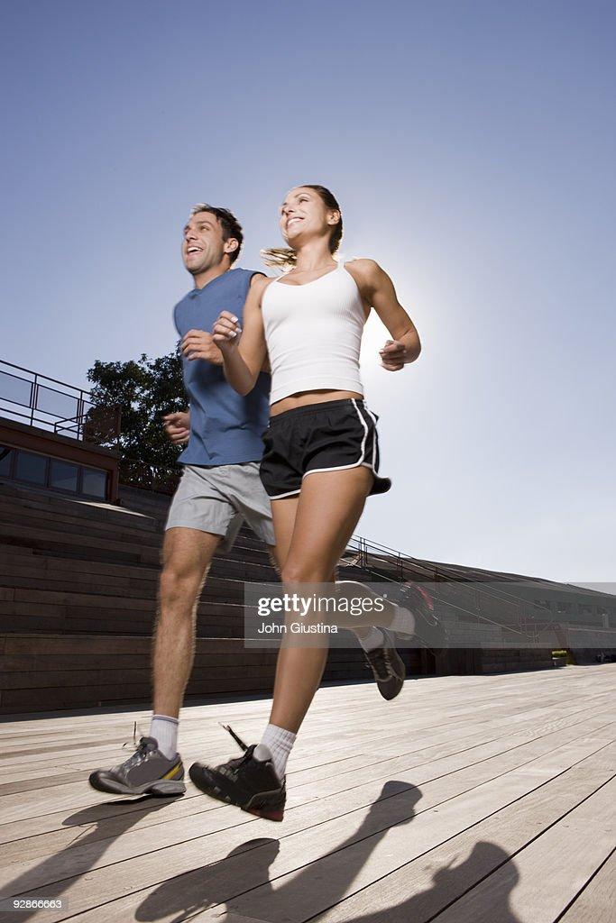Man and woman jogging on boardwalk. : Stock Photo