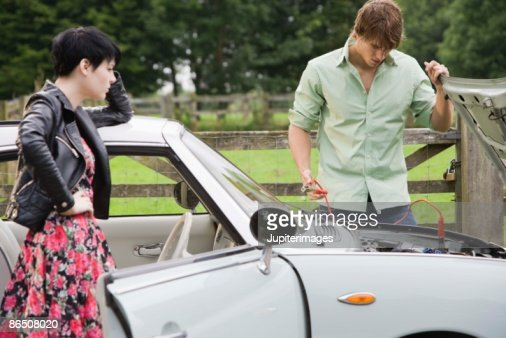 Man and woman jumping car battery : Stock Photo