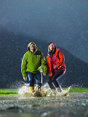 Man and woman jumping in a rain puddle.