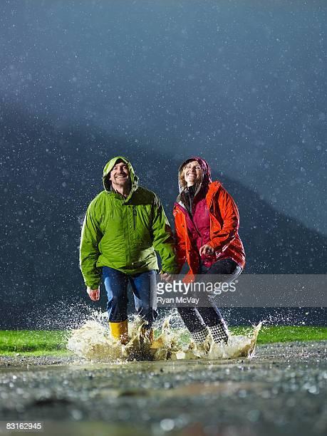 Hombre y mujer saltar en un charco tipo lluvia.